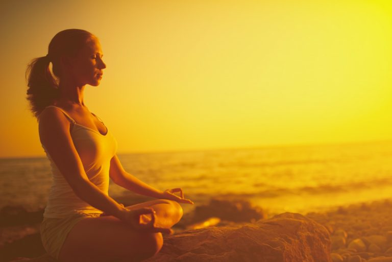 woman sitting in lotus position at sunset on beach shoreline