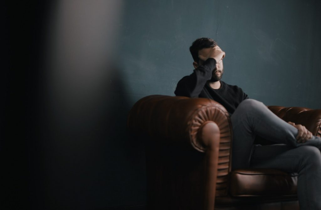 man sitting with hand over head