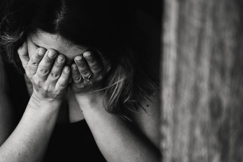 photo of sad woman with hands over her eyes