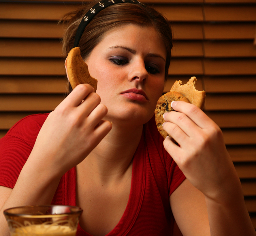 Image of a girl eating multiple cookies