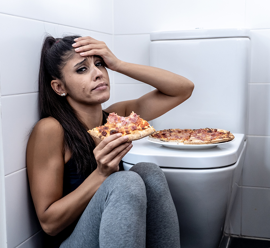 Image of a girl eating pizza next to a toilet